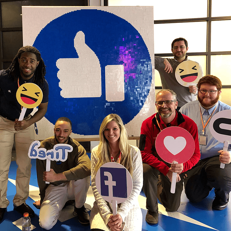 Students and staff standing in front of a Facebook的 icon and holding signs.