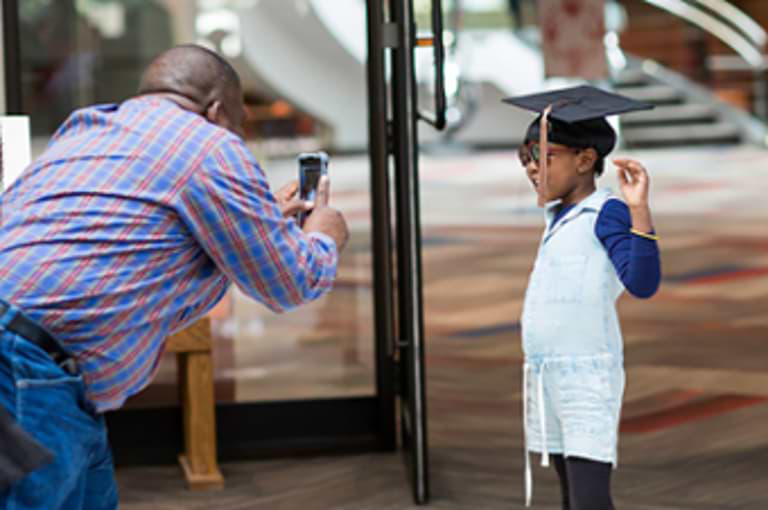 A man taking a photo of a child in a graduation cap